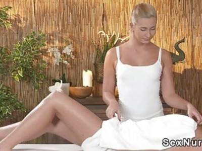 Blonde masseuse rubs brunettes cunt in massage room